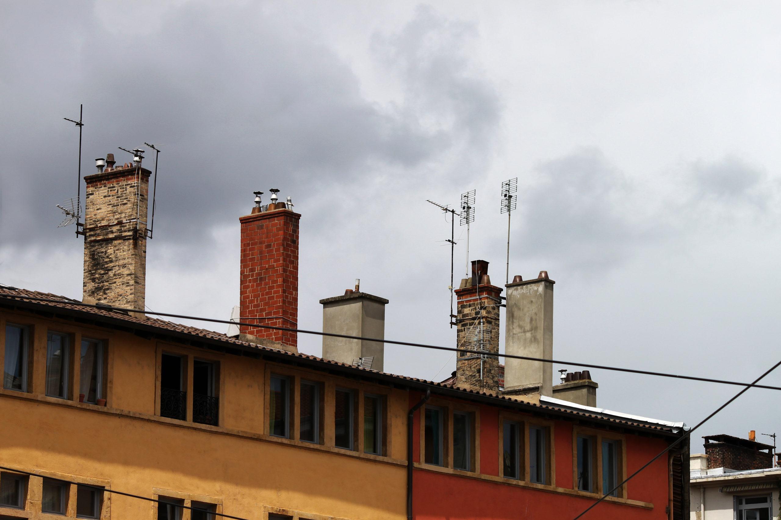 Cheminées sur les toits. Orange et ocre. Ciel gris, nuageux.