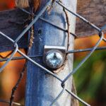 Macro. Barrière en métal et barrière en bois. Branche sèche coincée entre le métal.