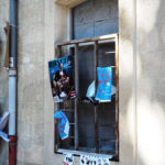 fenêtre murée, avec barreaux et affiches