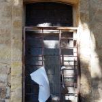 fenêtre murée, avec barreaux et une affiche déchirée, verso uniquement
