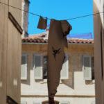 lambeau d'affiche suspendu entre deux murs dans une ruelle, arrière plan flou sur une maison