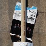 """Gros plan sur une affiche (pour le spectacle """"no limit"""") coincée derrière un poteau"""