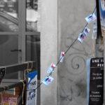 un coin de rue avec quelques affiches sur une barrière et un poteau, une ribambelle d'affichettes entre les deux