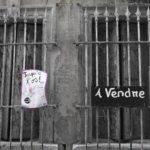 """façade avec deux fenêtres grillagées et aux volets fermés ; une affiche """"jusqu'à l'os"""" et un panneau """"à vendre"""""""