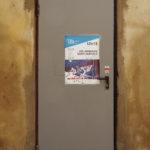 un mur, une porte au milieu, et une affiche de spectacle sur la porte